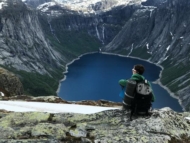 O homem com uma mochila admira a deslumbrante paisagem da montanha Foto gratuita