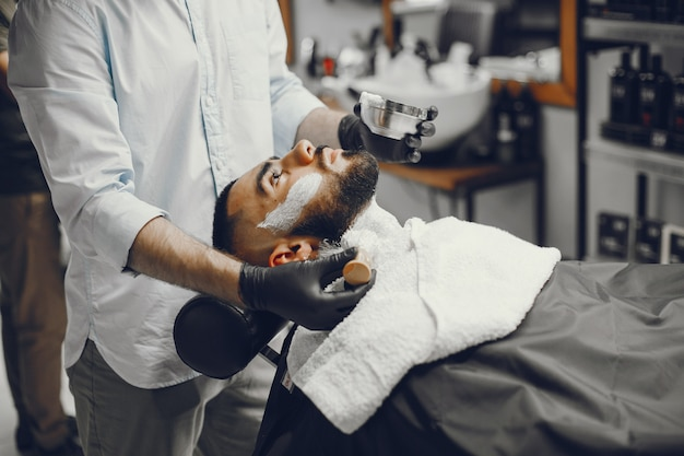 O homem corta a barba na barbearia. Foto gratuita