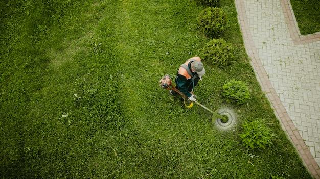 O homem cortador de grama corta a grama a vista de cima Foto Premium