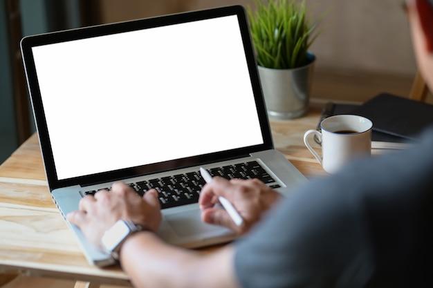 O homem da vista lateral que trabalha com portátil está na mesa de trabalho em um escritório conner Foto Premium