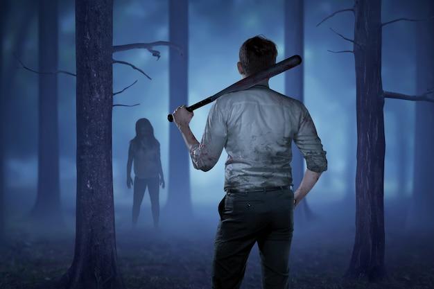 O homem de camisa ensangüentada segurando um pau com sangue quer bater a zumbi dama Foto Premium