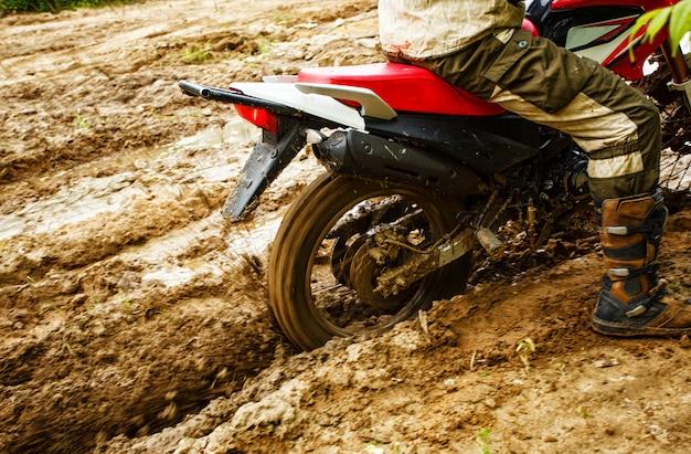 O homem de moto anda pela lama Foto Premium