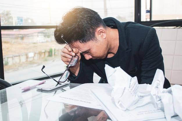 O homem de negócio asiático novo está trabalhando na pressão no escritório brilhante. Foto Premium