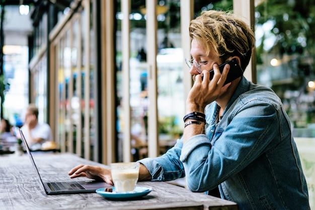 O homem de negócio atrativo novo em um café trabalha para um portátil, bebe o café. Foto gratuita