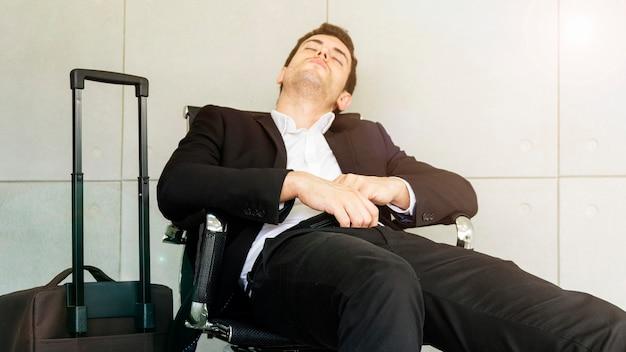 O homem de negócio é cansado e sente sonolento e senta-se na cadeira durante a espera do negócio que viaja no aeroporto. Foto Premium