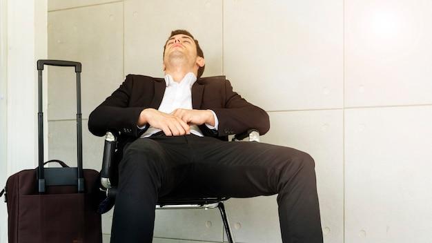 O homem de negócio está cansado e sente sonolento e senta-se na cadeira. Foto Premium