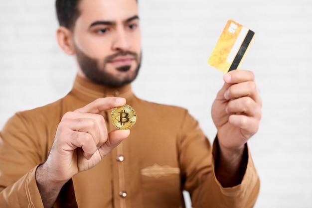 O homem de negócios árabe mantém o bitcoin dourado em uma mão e o cartão de crédito dourado em outro. ele veste uma camisa bege com um padrão. o close-up foi feito no fundo branco do estúdio. Foto Premium