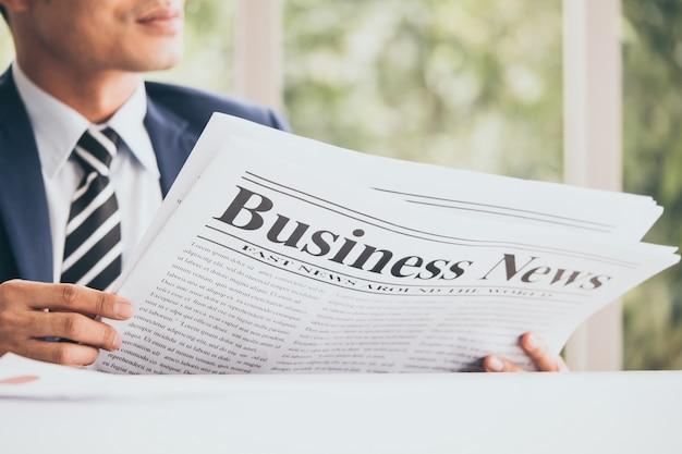 O homem de negócios asiático é de assento e de leitura a notícia de um jornal no escritório. Foto Premium