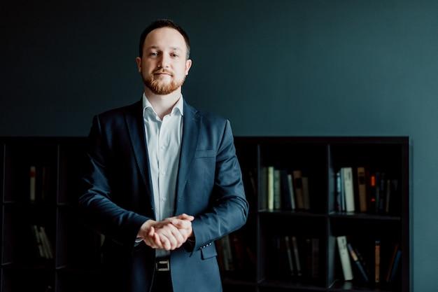 O homem de negócios bem sucedido em um terno está estando no escritório com suas mãos dobradas. Foto Premium