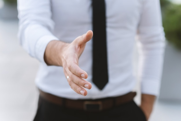 O homem de negócios do homem em uma camisa e em uma gravata brancas dá uma mão para um cumprimento. Foto Premium