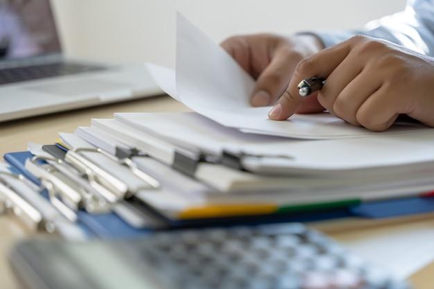 O homem de negócios documenta papéis do relatório comercial, succes do trabalho analisa planos do original Foto Premium