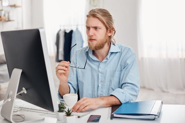 O homem de negócios masculino pensativo concentrado sério na camisa azul mantém espetáculos à disposição, trabalha no computador, pensa no relatório financeiro. gerente barbudo ou freelancer bebe café, gera idéias Foto gratuita