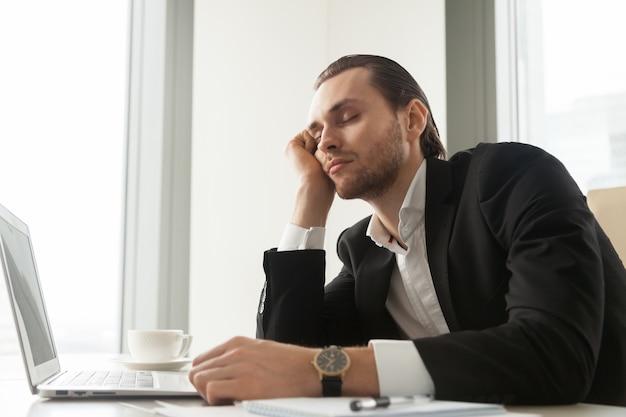 O homem de negócios novo cochilou na frente do portátil no trabalho. Foto gratuita