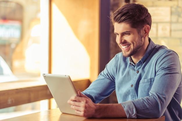 O homem de negócios novo considerável está usando uma tabuleta. Foto Premium