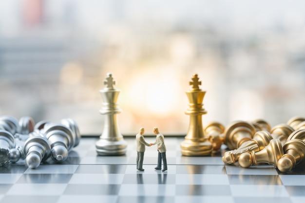 O homem de negócios pequeno figura a verificação da mão no tabuleiro de xadrez com partes de xadrez. Foto Premium