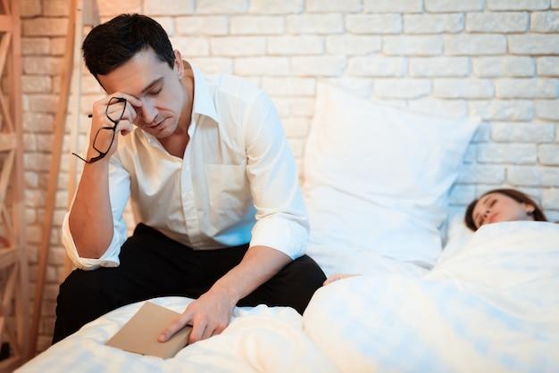 O homem de negócios senta-se na cama ao lado da mulher branca e lê-se o livro. Foto Premium