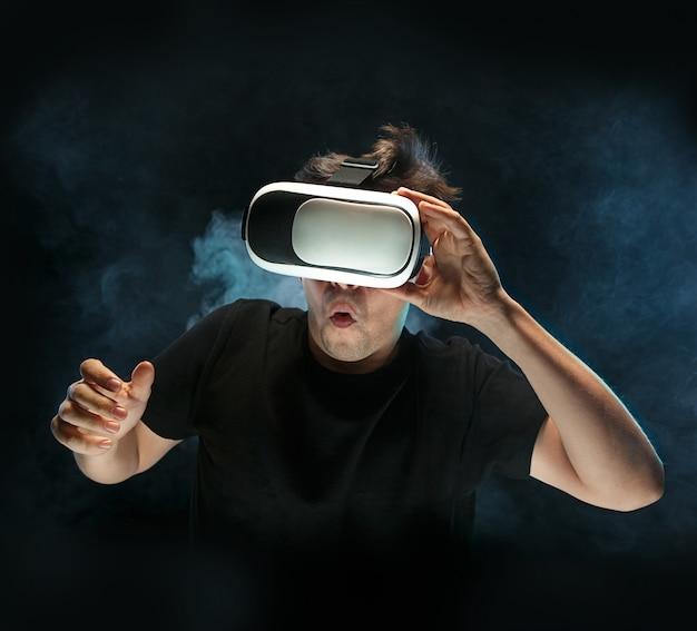 O homem de óculos de realidade virtual. conceito de tecnologia do futuro. fumarento preto do estúdio Foto gratuita