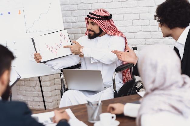 O homem deficiente mostra diagramas financeiros no escritório. Foto Premium