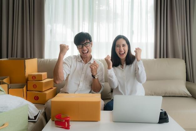 O homem e a mulher asiáticos estão vendendo on-line via computador internamente e muito satisfeitos quando há muitos pedidos. empreendedor de pequenas empresas startup pme ou conceito freelance Foto Premium