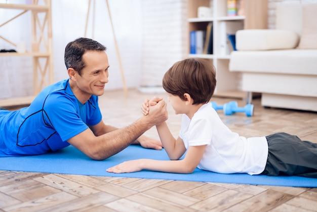 O homem e o menino estão envolvidos em luta de braço. Foto Premium