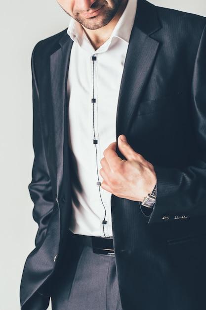 O homem em um terno clássico luxuoso levanta em uma sessão de foto. ele segura uma jaqueta preta com os dedos Foto Premium