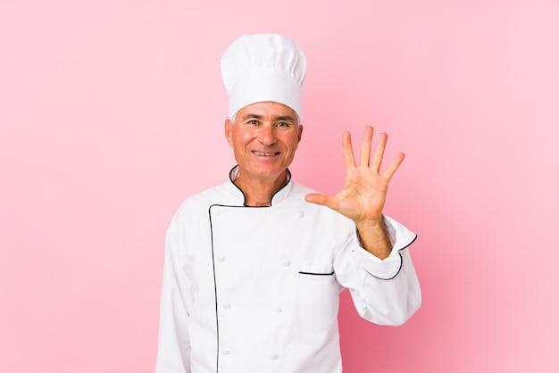O homem envelhecido médio do cozinheiro isolou o número mostrando alegre de sorriso cinco com dedos. Foto Premium