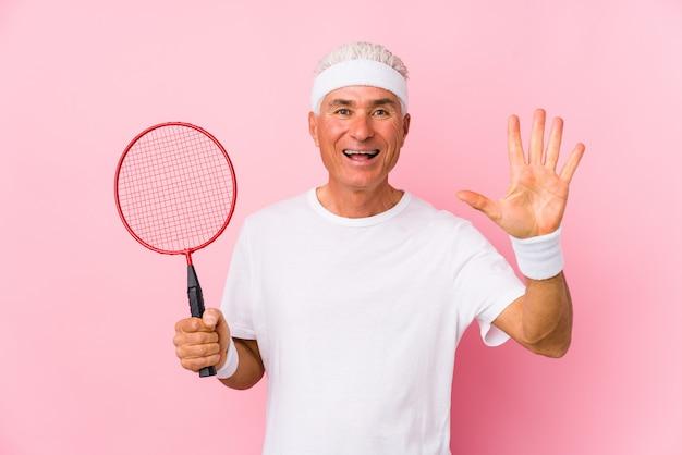 O homem envelhecido médio que joga o badminton isolou o número mostrando alegre de sorriso cinco com dedos. Foto Premium