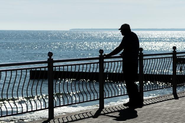 O homem envelhecido sonha com aventuras da vida, viagens passadas e olha para o mar. vista traseira traseira, copie o espaço. o velho viúvo com câncer sente falta da esposa. tempo ensolarado e mar azul limpo. Foto Premium