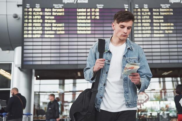 O homem espera seu vôo no aeroporto. Foto gratuita