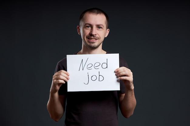 O homem está à procura de trabalho, desemprego e crise. emoções diferentes no rosto, um sinal nas mãos Foto Premium