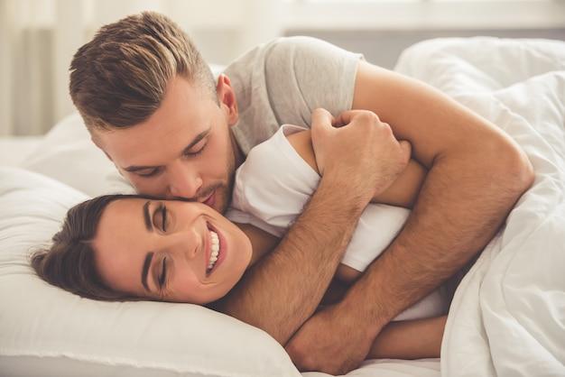 O homem está abraçando e beijando sua esposa sorridente na bochecha Foto Premium