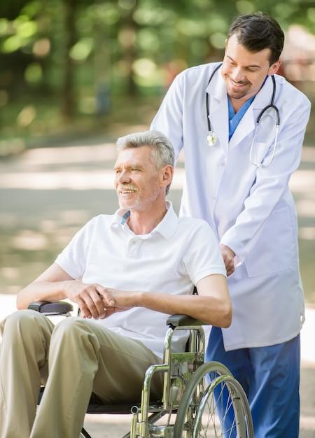 O homem está andando com o paciente sênior na cadeira de rodas. Foto Premium