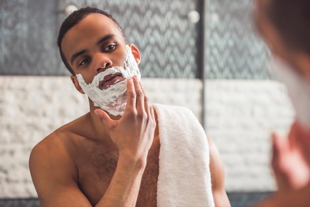 O homem está aplicando a espuma de rapagem ao olhar no espelho. Foto Premium
