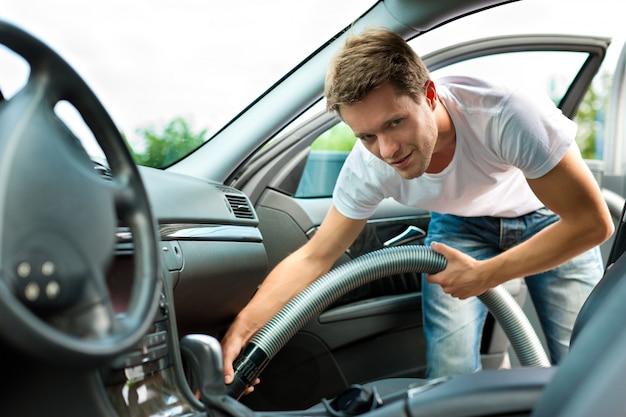 O homem está aspirando ou limpando o carro Foto Premium