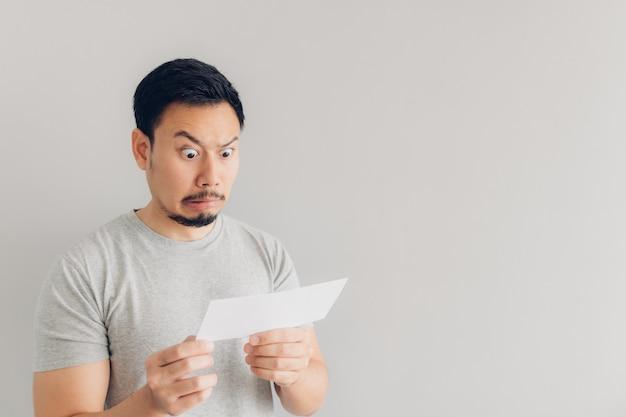 O homem está chocado e surpreso com a mensagem de correio branco ou a conta. Foto Premium