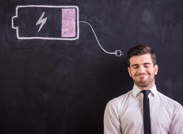 O homem está de encontro ao quadro-negro com a bateria do desenho baixa. Foto Premium