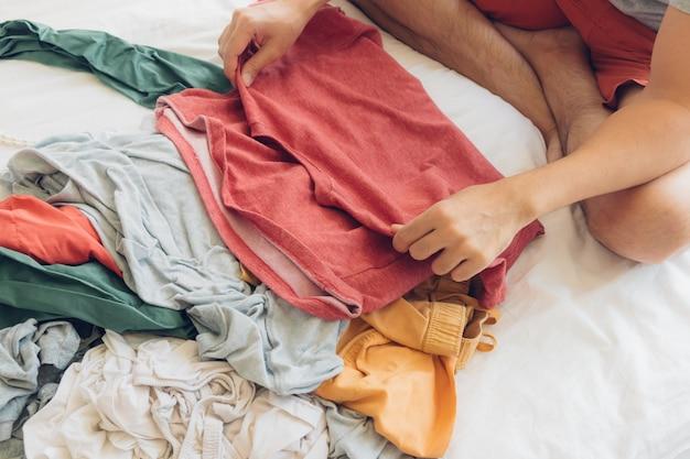 O homem está dobrando e arrumando as roupas na cama. Foto Premium