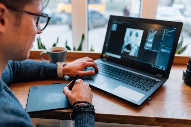 O homem está editando fotos no laptop, usando a mesa digitalizadora e o visor interativo com caneta Foto gratuita