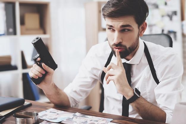 O homem está guardando a arma e shushing ao olhar fotos. Foto Premium