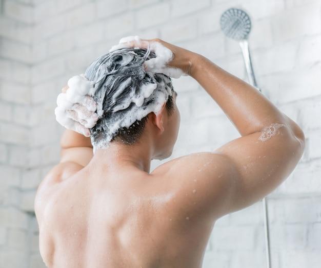 O homem está lavando o cabelo, ele usa xampu. Foto Premium