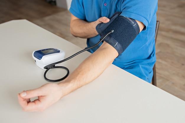 O homem está medindo a pressão sanguínea com o monitor na casa. Foto Premium