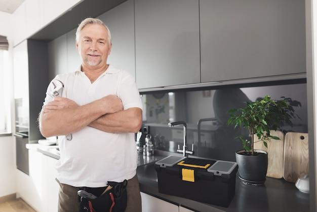 O homem está na cozinha. ele tem uma chave de cromo na mão. Foto Premium
