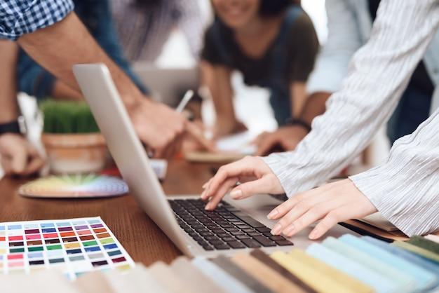 O homem está sentado no laptop. ele trabalha em um escritório criativo. Foto Premium