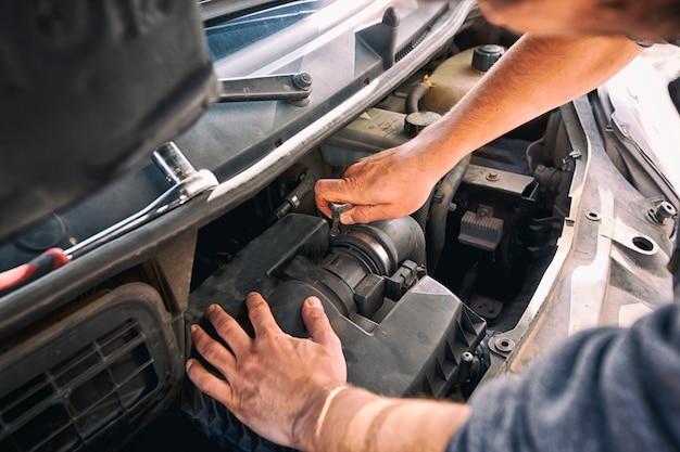 O homem está tentando consertar o carro velho quebrado em casa Foto Premium
