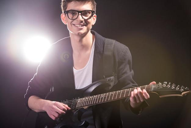 O homem está tocando violão no quarto escuro com luzes atrás dele. Foto Premium