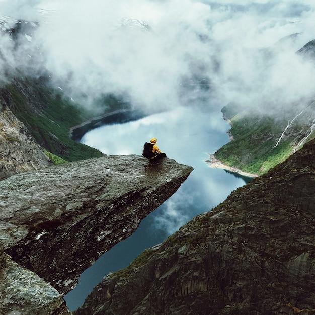 O homem fica no final de trolltunga antes das montanhas Foto gratuita