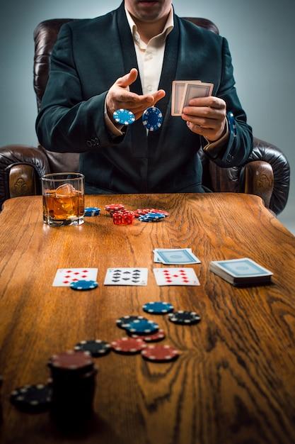 O homem, fichas para jogar, beber e jogar cartas Foto gratuita
