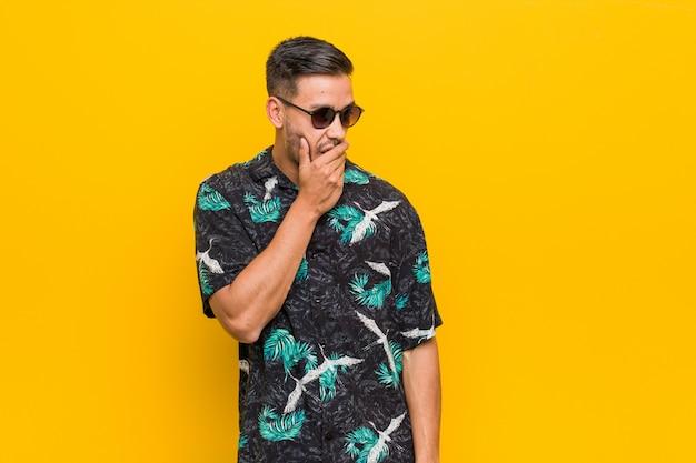 O homem filipino novo que veste a roupa do verão mantem as mãos sob o queixo, está olhando feliz de lado. Foto Premium