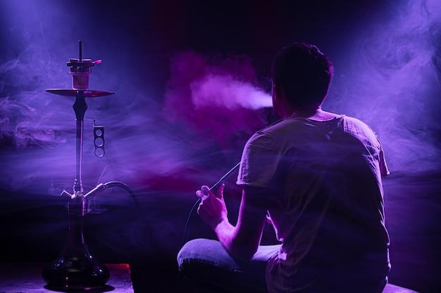 O homem fumando o clássico shisha Foto gratuita