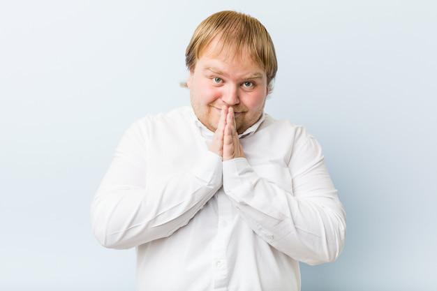 O homem gordo jovem ruiva autêntica, segurando as mãos em rezar perto da boca, sente-se confiante. Foto Premium